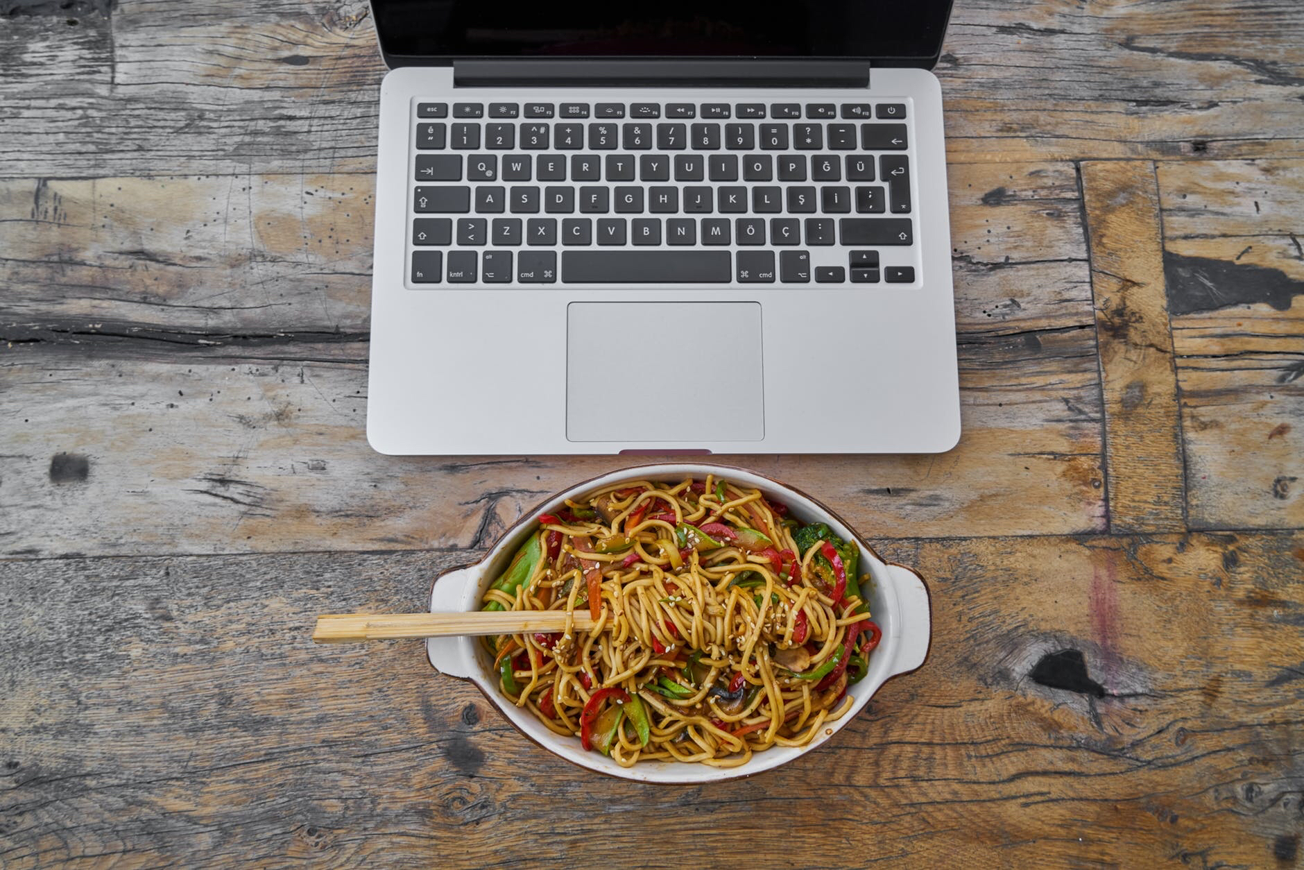Noodle dish in front of MacBook